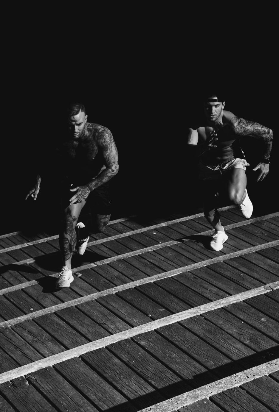 Two shirtless, muscular men racing.